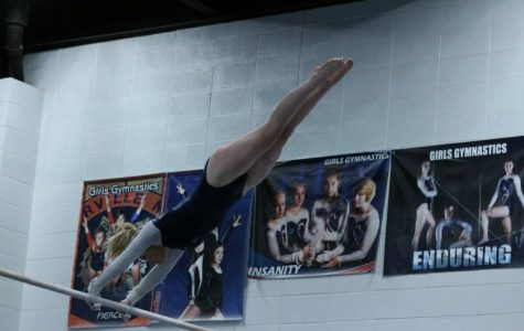 Junior Grace Ryan performs on the uneven bars