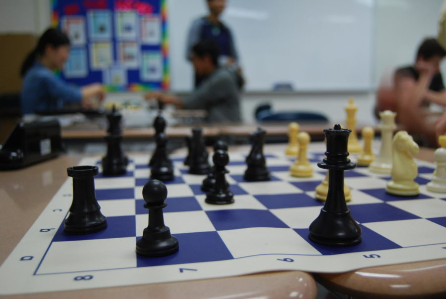 +A+chess+piece+is+placed+in+position+during+a+quick+game+between+two+students.