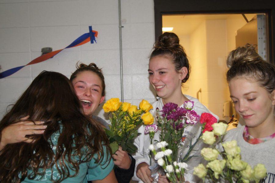 Senior Margot Steed shares a hug with junior Rachel Ostrowski as juniors Evie Pendlay and Chloe Einspar look on.