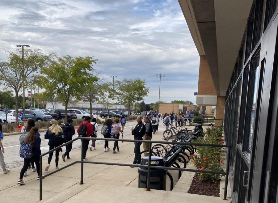 Students exit the building through the NPAC doors at 10:44 a.m. while police officers monitor the evacuation.